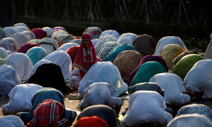 A girl attends Eid al-Adha prayers with others worshipers on the street in Jakarta