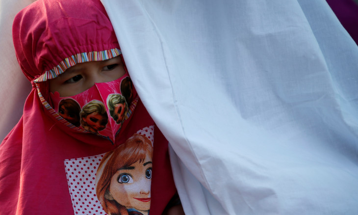 A face mask-wearing girl attends Eid al-Adha prayers