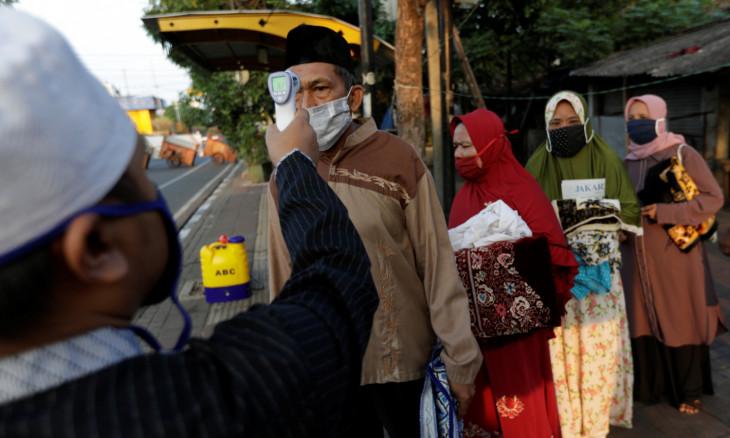 Temperature readings are taken for people attending Eid al-Adha prayers in Jakarta