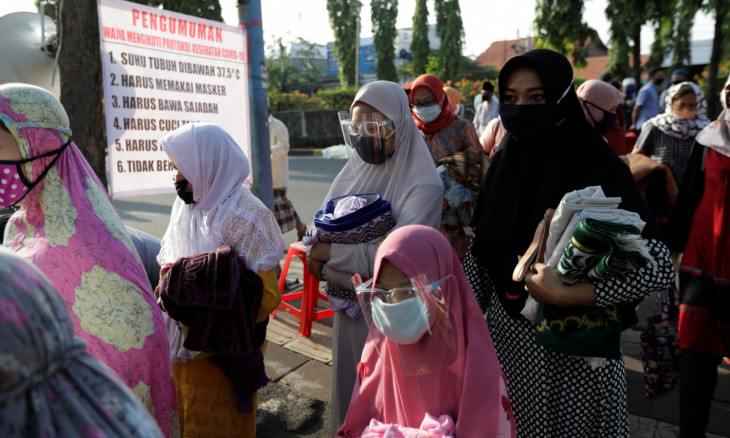 Face masks and shields wearing Indonesian Muslim women walk to attend Eid al-Adha prayers