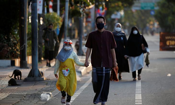 Indonesian Muslims walking to Eid al-Adha prayers wearing face masks