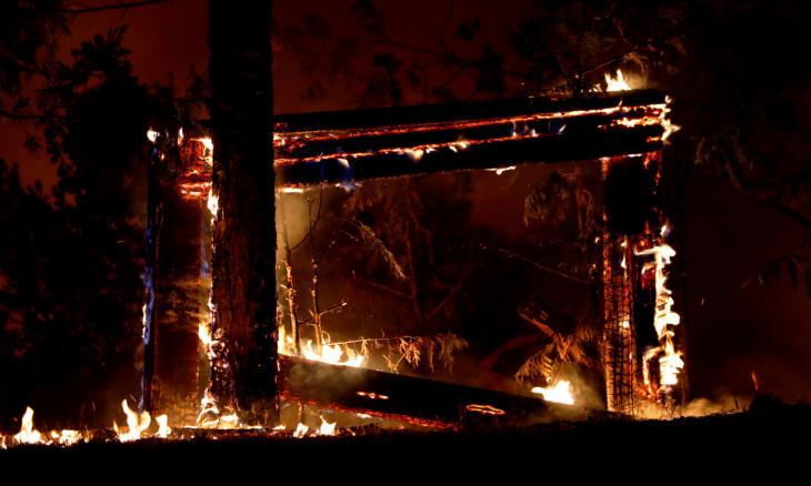 A sign engulfed in flames is seen during the Creek Fire