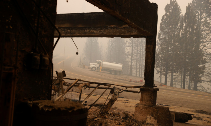 A water tender truck is seen through charred remains of the historical Cressman's General Store