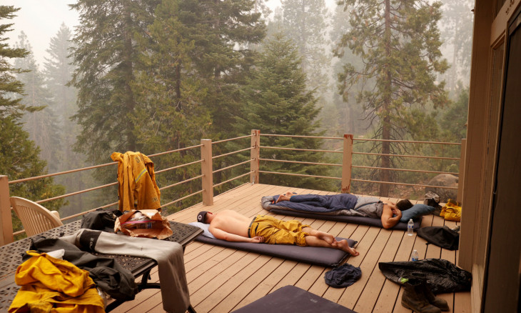 Two Cal OES mutual aid strike team firefighters rest on a deck