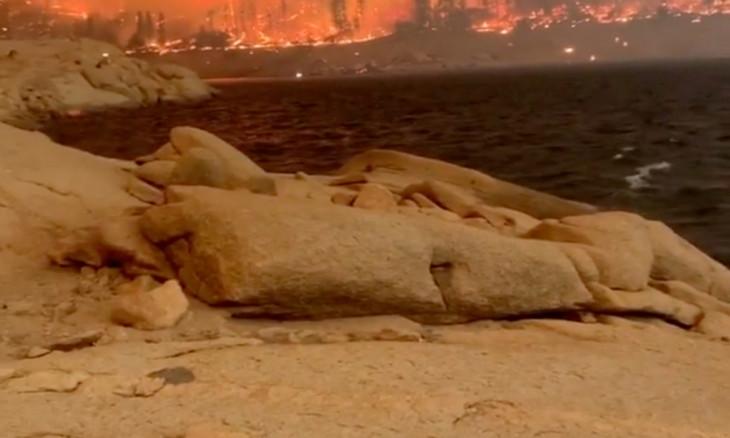 A fire surrounds Mammoth Pool Reservoir