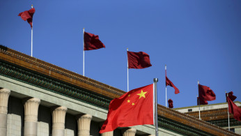 Chinese flag waves in front of the Great Hall of the People in Beijing