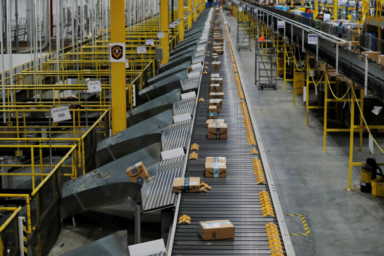 Amazon packages are pushed onto ramps leading to delivery trucks by a robotic system