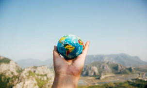 Person holding world globe facing mountains.