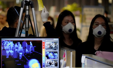 Passengers wearing masks to prevent contracting coronavirus walk past a thermal camera upon their arrival at Incheon International Airport in Incheon