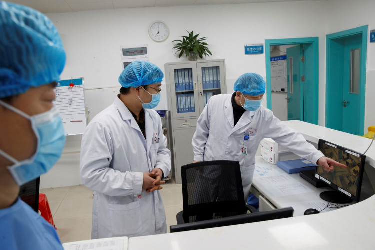 Doctors look at a screen that shows the ward where patients who are infected with the coronavirus