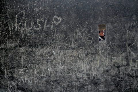 A man walks past a fort wall covered with graffiti on Valentine's Day in Mumbai