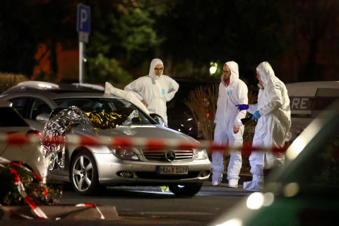 Forensic experts work around a damaged car after a shooting in Hanau near Frankfurt