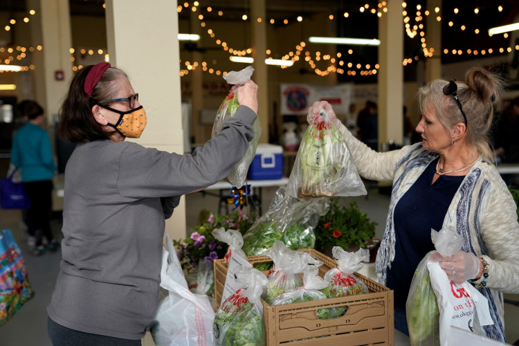 Sandy Meir, left, buys produce from Debby Taylor while wearing a mask at the Farmers Public Market in Oklahoma City, Oklahoma, U.S.