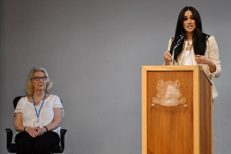 Britain's Meghan, Duchess of Sussex speaks as Geraldine Dear looks on during a school assembly as part of a visit to Robert Clack School in Essex