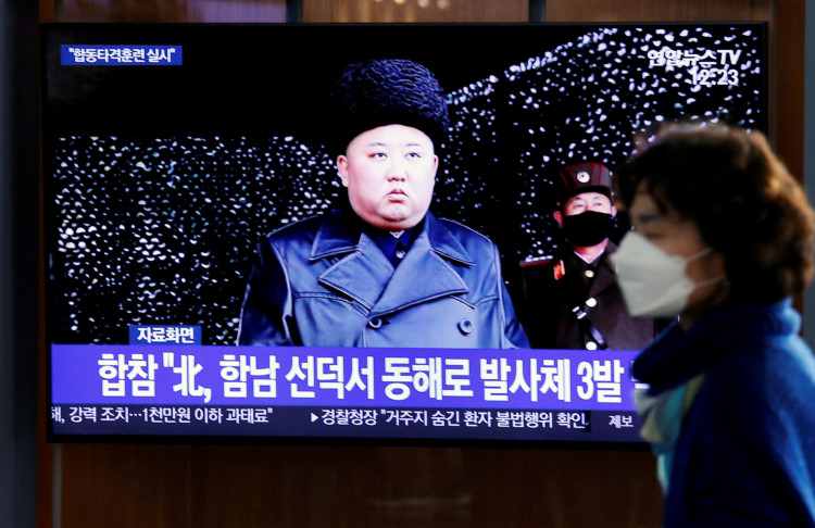 A woman walks past a TV broadcasting file footage for a news report on North Korea firing an unidentified projectile, in Seoul, South Korea, March 9, 2020