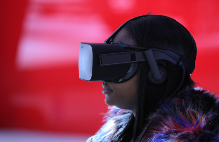 A woman wears VR goggles as she sits in a virtual reality booth at the North American International Auto Show in Detroit, Michigan, U.S., January 15, 2019.