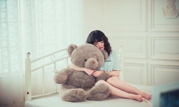 Woman hugging gray bear.