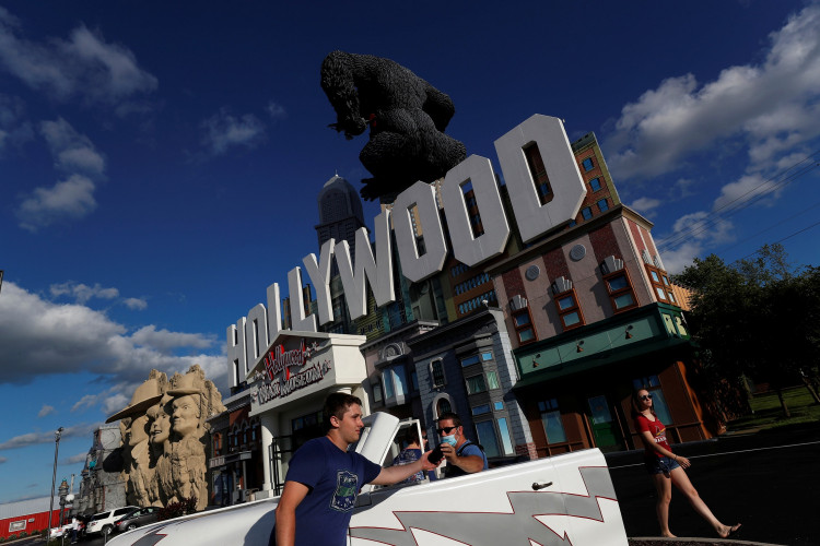 A man wearing a protective face mask hands a mobile phone outside the Hollywood Wax Museum in the family vacation destination town of Branson, Missouri, U.S.