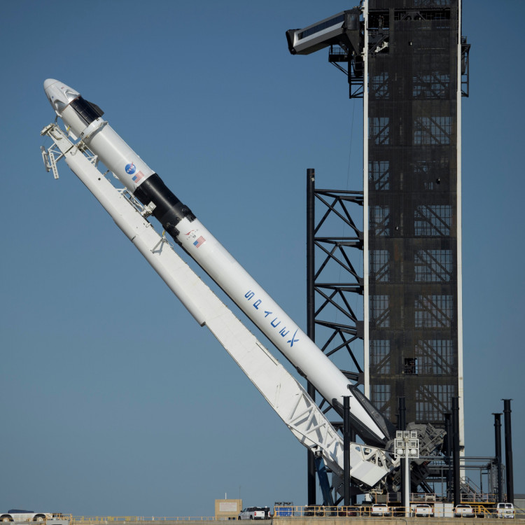A SpaceX Falcon 9 rocket with the company's Crew Dragon spacecraft onboard is raised into a vertical position on the launch pad at Launch Complex 39A at NASA's Kennedy Space Center