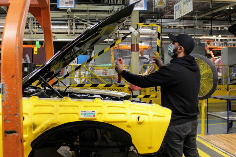 An operator at FCA's Brampton Assembly Plant installs a removable plexiglas partition in the engine compartment of a Dodge Challenger to help staff maintain social distancing against the coronavirus disease