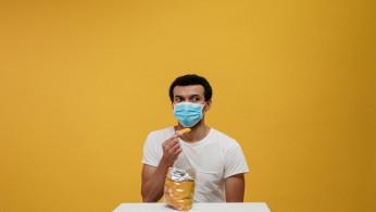 Man in white t-shirt eating chips.