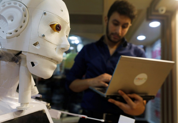 The Egyptian mechanical engineer, Mahmoud El komy, 26, is seen beside the remote-controlled robot that he build to test people for the coronavirus by running PCR tests, limiting exposure to suspected cases, in Cairo