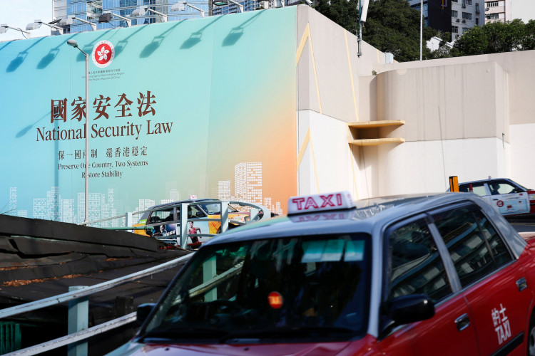 Taxis drive past government-sponsored advertisement promoting the new national security law