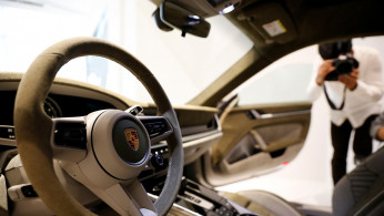 The logo of Porsche is pictured on the steering wheel of a Porsche 911 sports car