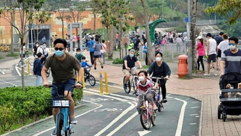 People wearing masks on bicycles in Hong Kong