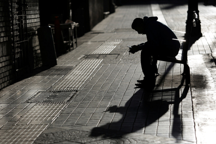 A man checks his phone while sitting on a bench