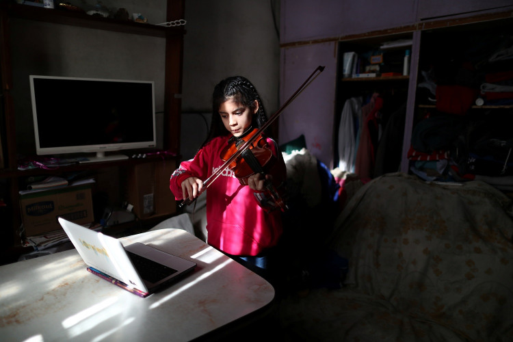 Marcela, 12, member of the Buenos Aires children's and youth orchestra program, practices her violin during a video call at home during the coronavirus pandemic