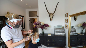 A hairstylist wearing a face shield works on the hair of the client Susan Hepple at the Hair by Reiss salon