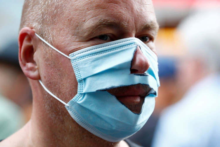 A demonstrator wears a mask that has been cut out