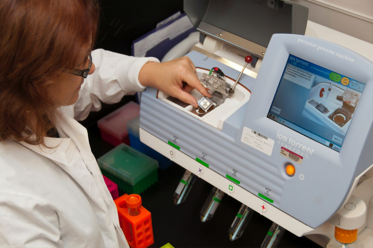 A female lab technician loading a semiconductor DNA sequencing chip