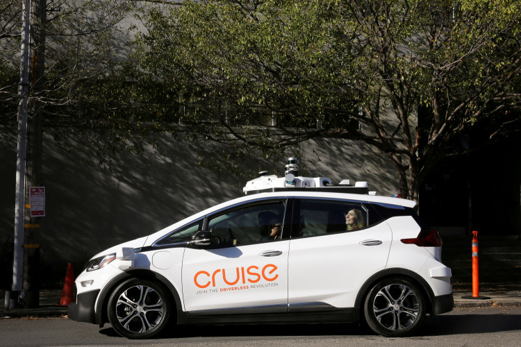 FILE PHOTO: A woman smiles in the back seat of a self-driving Chevy Bolt EV car during a media event by Cruise, GM's autonomous car unit, in San Francisco