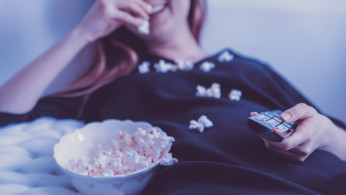 happy woman eating popcorn