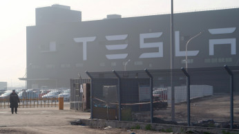 FILE PHOTO: A Tesla sign is seen on the Shanghai Gigafactory of the U.S. electric car maker in Shanghai, China, Dec. 30, 2019