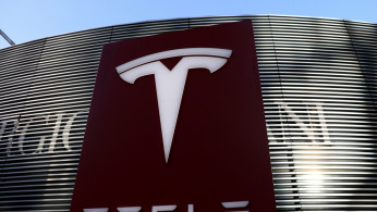 Logo of the electric vehicle maker Tesla is seen near a shopping complex in Beijing