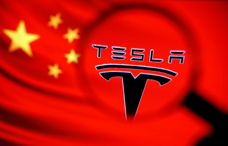 Chinese flag and Tesla logo is seen through a magnifier in this illustration