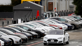 FILE PHOTO: A Tesla Model S electric vehicle drives along a row of occupied Superchargers