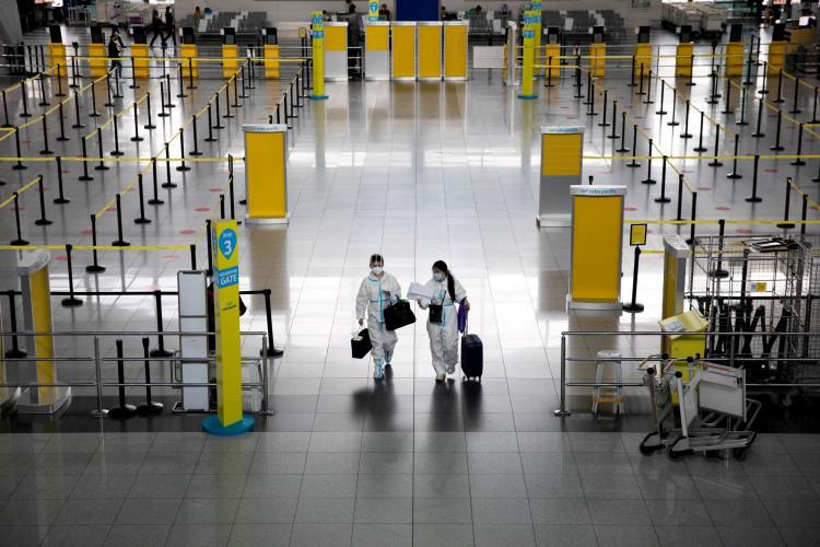Passengers wearing hazmat suits walk inside the Ninoy Aquino International Airport in Paranaque, Metro Manila.