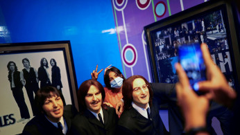 Visitors take photos with the wax figures of the Beatles at a wax museum.