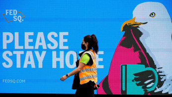 FILE PHOTO: An essential worker walks past a 'Please Stay Home' sign
