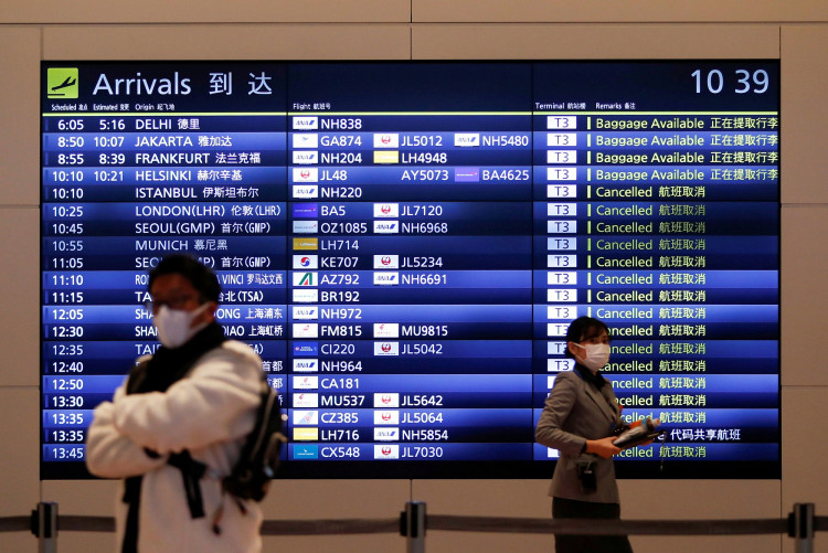 A visitor and an airline company staff member wearing protective face masks are seen at the arrival gate of the international flight terminal at Tokyo International Airport