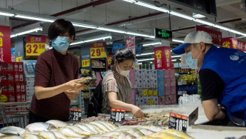 People look at fresh seafood in a supermarket in Beijing, China.