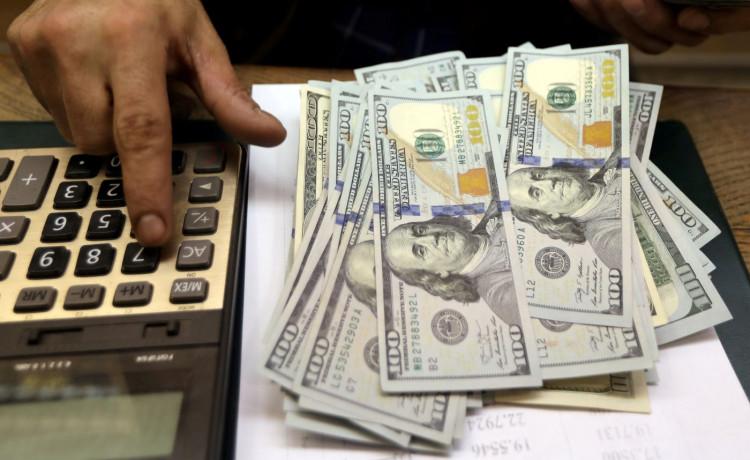 An employee counts U.S. dollar bills at a money exchange.