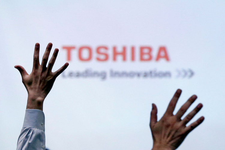 Reporters raise their hands during a Toshiba news conference in Tokyo, Japan.