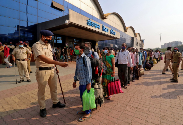 A police officer maintains order as people wearing protective masks wait in line to enter the Lokmanya Tilak Terminus railway station