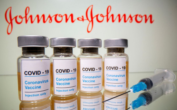 Vials with a sticker reading, 'COVID-19' are seen in front of a displayed Johnson & Johnson logo.