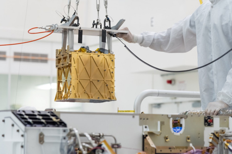 Technicians at NASA's Jet Propulsion Laboratory lower the Mars Oxygen In-Situ Resource Utilization Experiment (MOXIE) instrument into the belly of the Perseverance rover